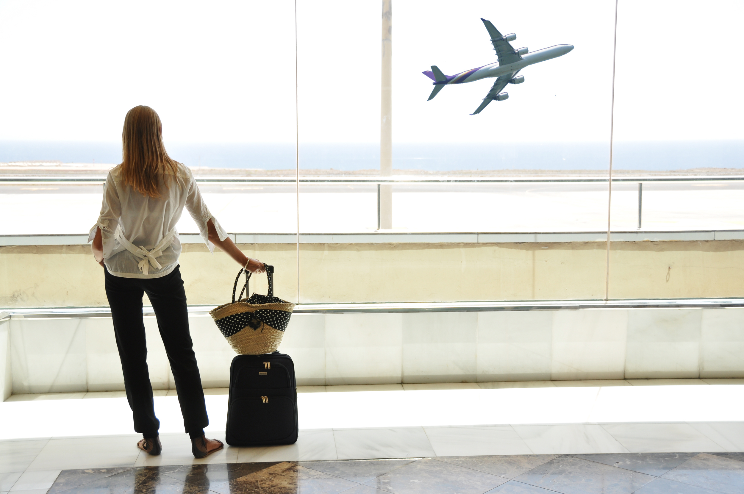 bigstock-girl-at-the-airport-window-loo-26611490